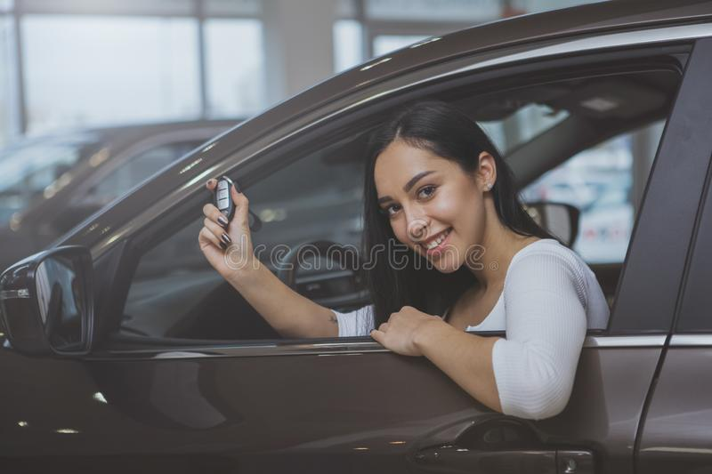 Lovely young woman buying new car at the dealership. Cheerful beautiful woman smiling happily, holding car key sitting in her new automobile at dealership salon stock image