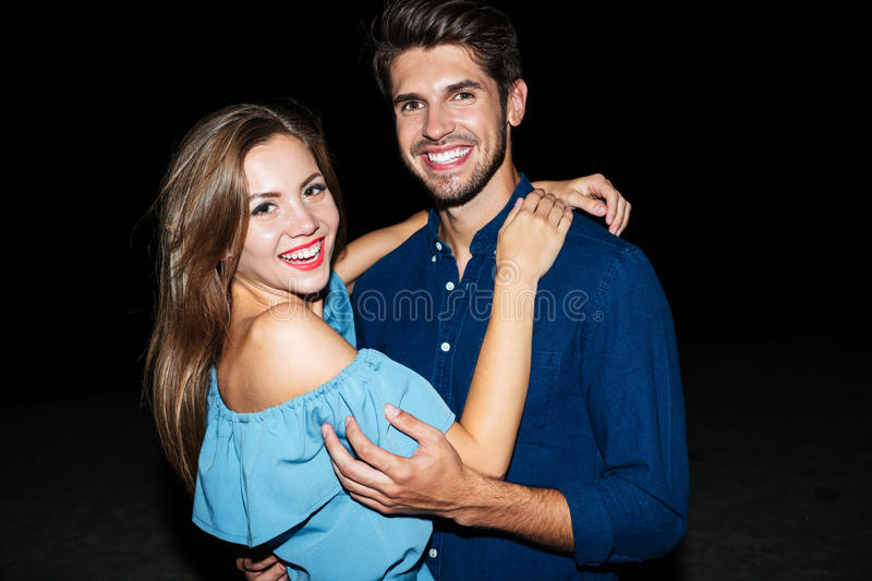 Cheerful beautiful young couple standing on the beach at night royalty free stock photography