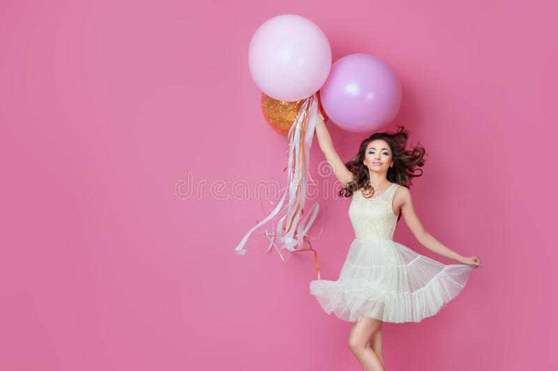 Cheerful Beautiful young girl in dress with sparkle and pink helium balloons enjoying birthday photoshoot dancing and smiling on p. Ink background Cute woman royalty free stock photography