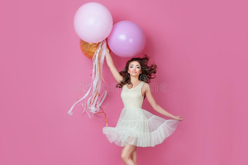 Cheerful Beautiful young girl in dress with sparkle and pink helium balloons enjoying birthday photoshoot dancing and smiling on p stock images