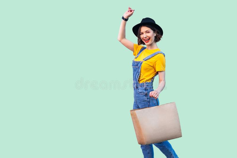 Cheerful beautiful young girl in hipster wear in denim overalls and black hat holding shop bag toothy smile, celebrating great royalty free stock photo