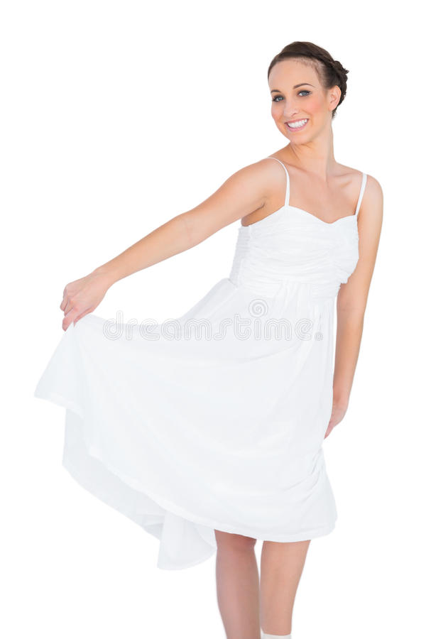 Cheerful beautiful young model in white dress dancing stock photo