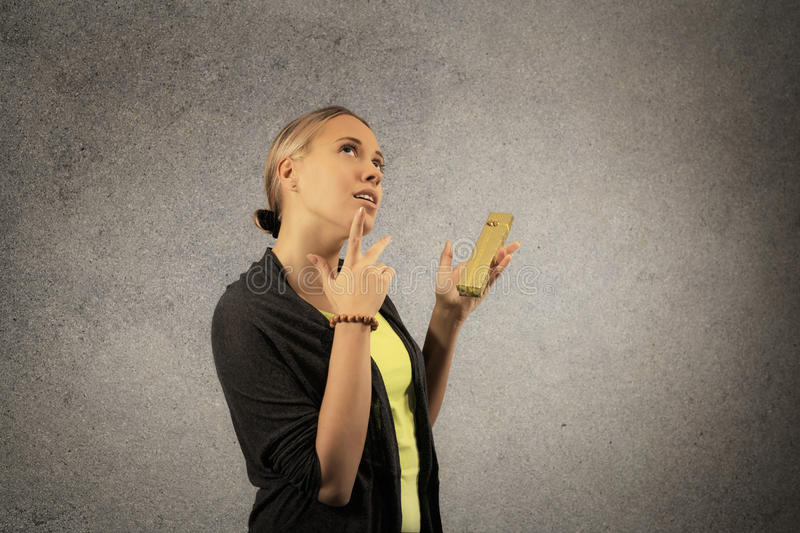 Cheerful beautiful young woman in casual cloths wonder what is inside golden present box in her hands stock images