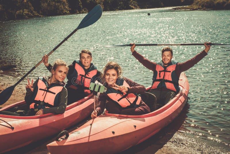 Cheerful best friends taking selfie in kayaks on a beach. royalty free stock image