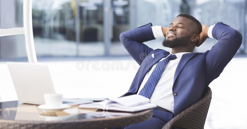 Cheerful black businessman relaxing in outdoor cafe, panorama. Successful business career. Black businessman relaxing after finishing work project in outdoor stock images