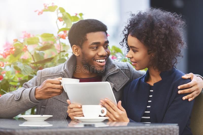 Cheerful african american couple shopping online, using tablet royalty free stock images