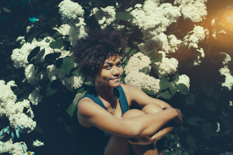 Cheerful black girl in front of wall of white flowers. Portrait of cute smiling black teen girl with curly afro hair sitting in private park in closed pose, in royalty free stock photos
