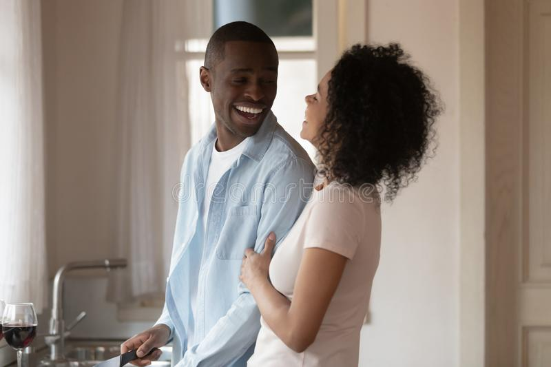 African couple cooking at home in the kitchen. Cheerful black guy hold knife prepare dinner chatting with beloved mixed race girl, 30s couple in love chatting royalty free stock images