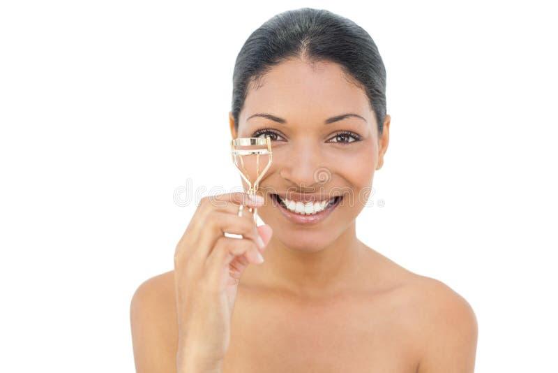 Cheerful black haired model holding eyelash curler. On white background royalty free stock photo