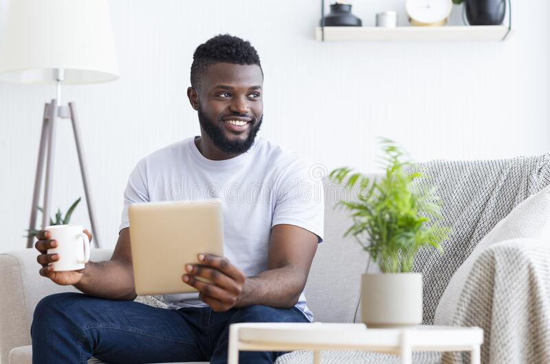 Cheerful black man with digital tablet and coffee looking away royalty free stock photography