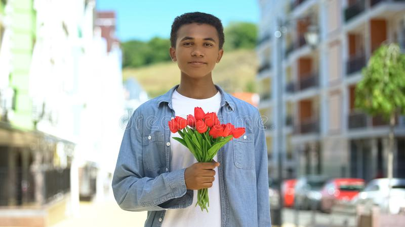Cheerful black teen boy holding bunch of tulips, international women day gift royalty free stock images