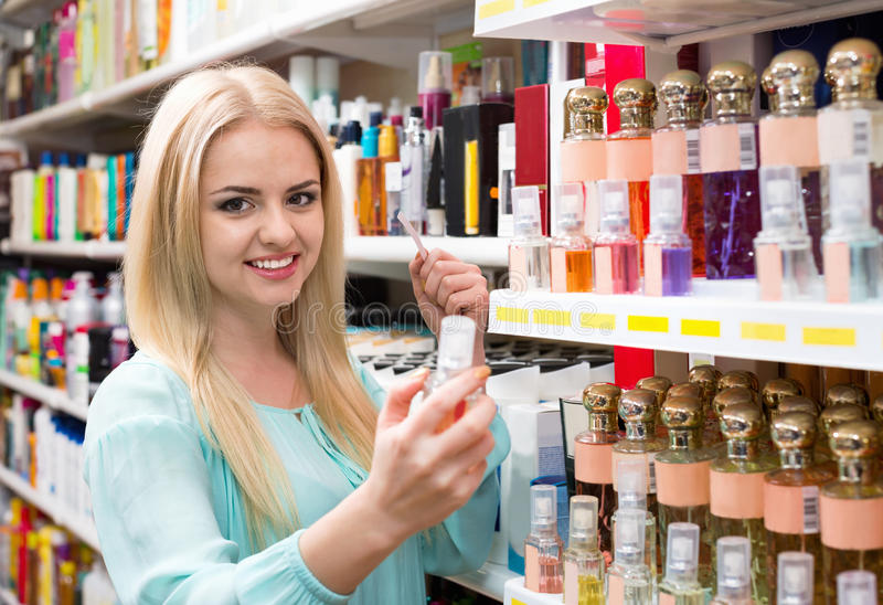 Cheerful blond girl buying perfume in fragrance section. Of supermarket stock photos