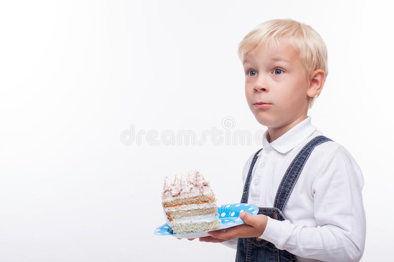 Cheerful blond schoolboy is carrying sweet food. Cute boy is holding a plate with piece of cake. He is standing and looking aside with surprise. Isolated and royalty free stock photos