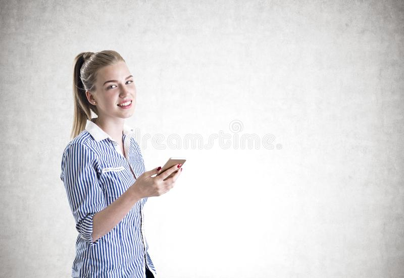 Cheerful blonde businesswoman, smartphone concrete stock image