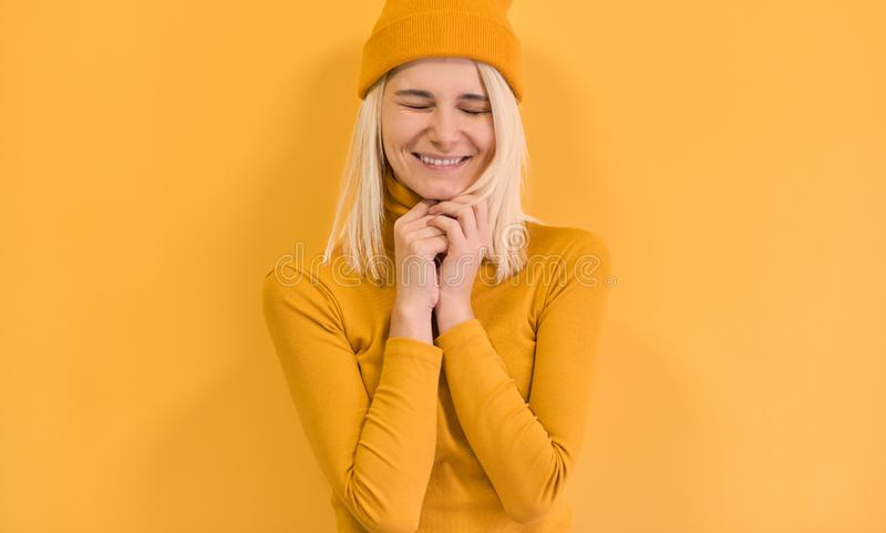 Cheerful blonde female with positive expression, close her eyes and smiling joyfully, wears yellow clothes, isolated over yellow royalty free stock photos