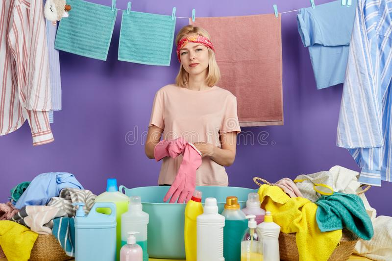 Cheerful blonde housewife in casual clothes putting on protective gloves royalty free stock image