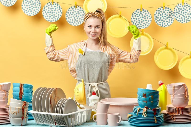 Cheerful blonde housewife in gray apron in green gloves showing biceps isolated stock photography