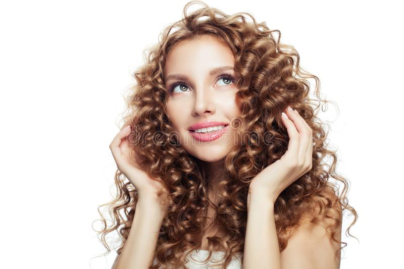 Cheerful blonde woman touching her hair her hand and looking up royalty free stock image