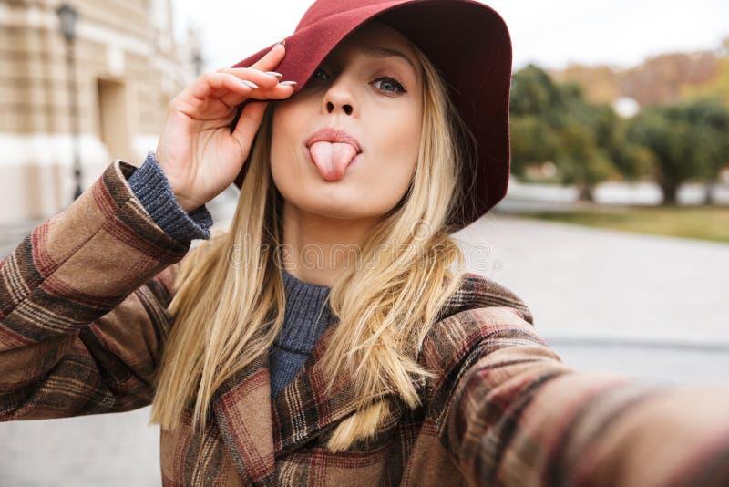 Cheerful woman wearing autumn coat walking outdoors, taking a selfie stock photos