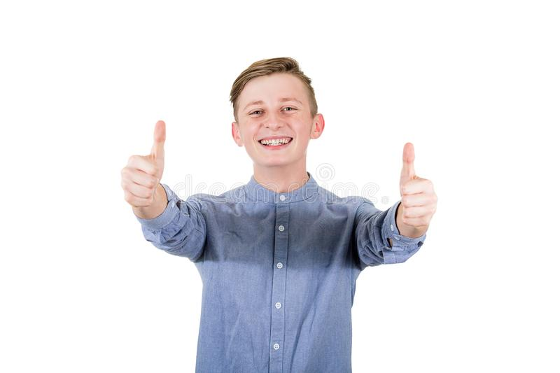 Cheerful boy adolescent showing double thumbs up, positive gesture, great feedback and approval, looking to camera with tooth. Smile isolated over white stock photo