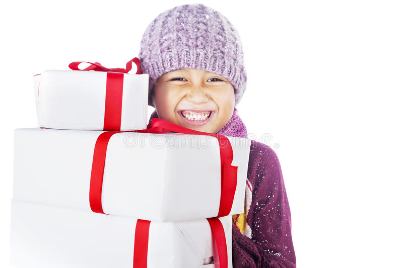Cheerful boy and Christmas gifts isolated in white. Boy wearing beany in winter is holding gifts cheerfully, isolated in white stock photography