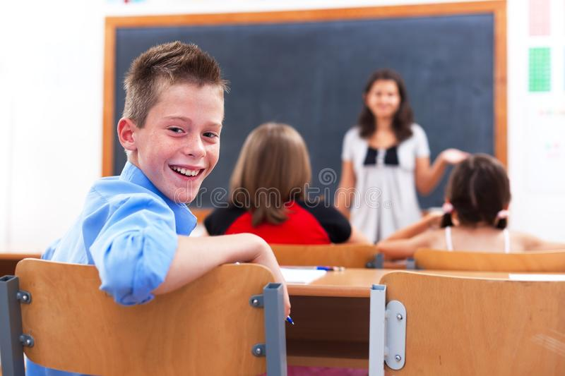 Cheerful boy in class room. Cheerful school boy looking back in class room while the teacher explains royalty free stock photography