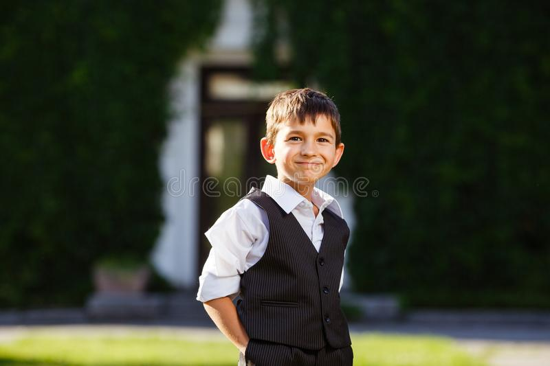 Cheerful boy in fashionable suit on green grass stock photography