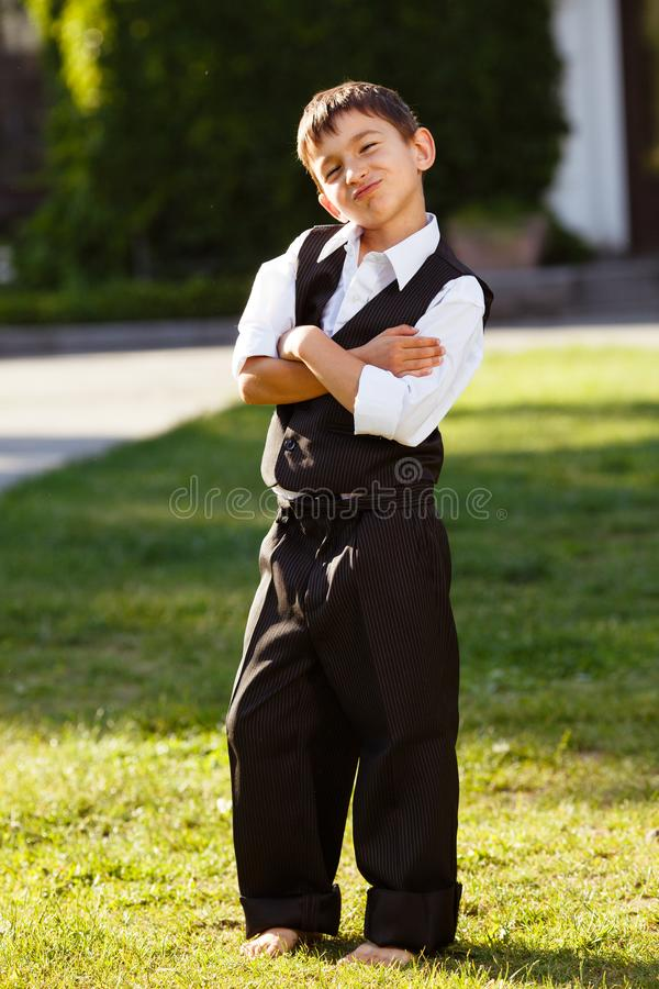 Cheerful boy in fashionable suit on green grass royalty free stock photography
