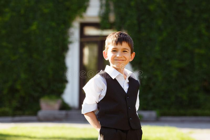 Cheerful boy in fashionable suit on green grass royalty free stock photo