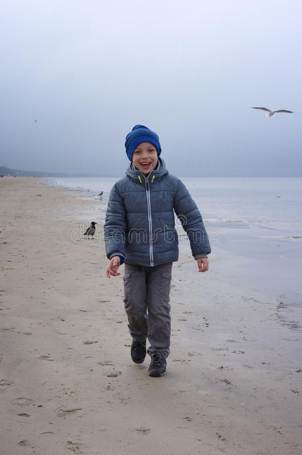 A cheerful boy feeds gulls on the seashore in winter, spring or autumn. many gulls are flying around. Cold day by the sea. royalty free stock photo