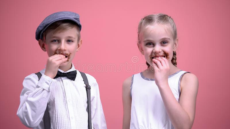Cheerful boy and girl smiling and eating chocolate candies, celebrating holiday royalty free stock photos