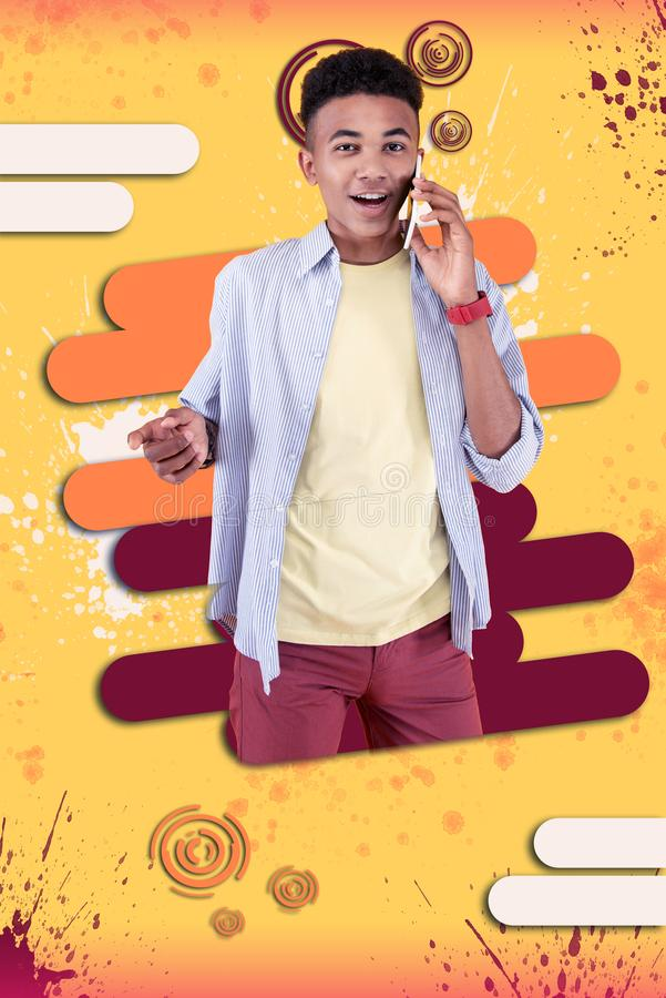 Happy boy holding his red smartphone feeling cheerful communicating with friend. Cheerful boy. Happy mulatto boy standing in front of graphic background holding stock image