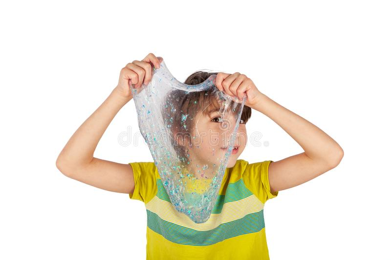 Cheerful boy holding a glitter slime and looking through its hole. Studio shot isolated on white royalty free stock image
