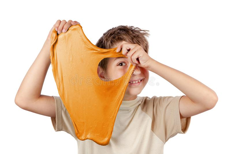 Cheerful boy holding a slime and looking throw its hole. Cheerful boy holding an orange slime and looking throw its hole. Studio isolated on white background royalty free stock photography