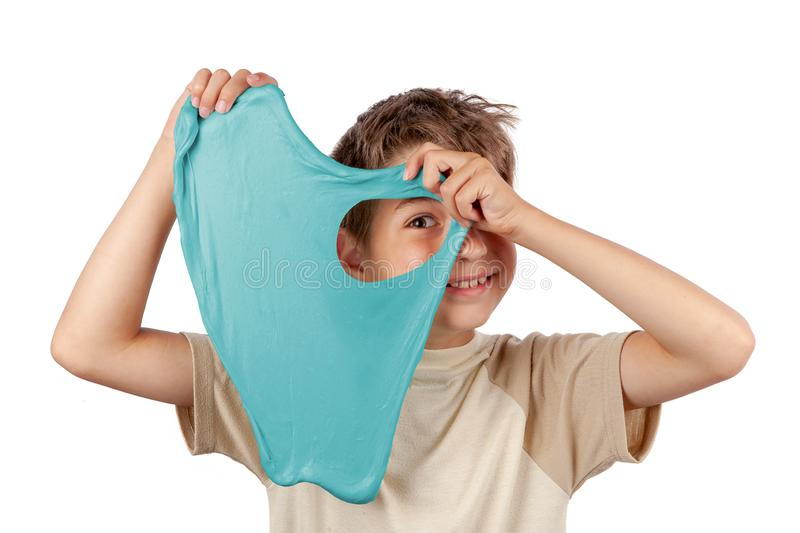 Cheerful boy holding a turquoise color slime toy. And looking through its hole. Studio isolated on white background royalty free stock photography