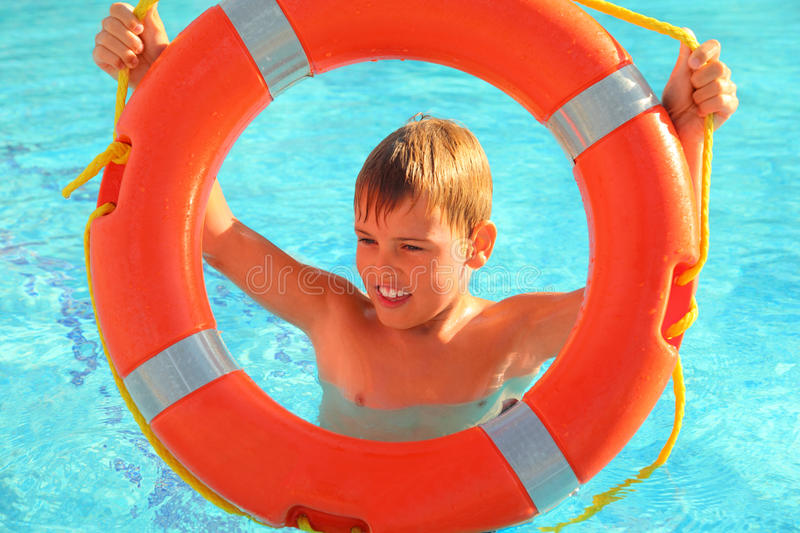 Cheerful boy looks through buoy from swimming-poo royalty free stock image