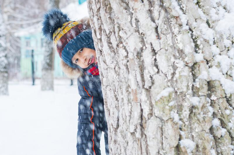 Cheerful boy looks out from behind a tree. winter walk royalty free stock images