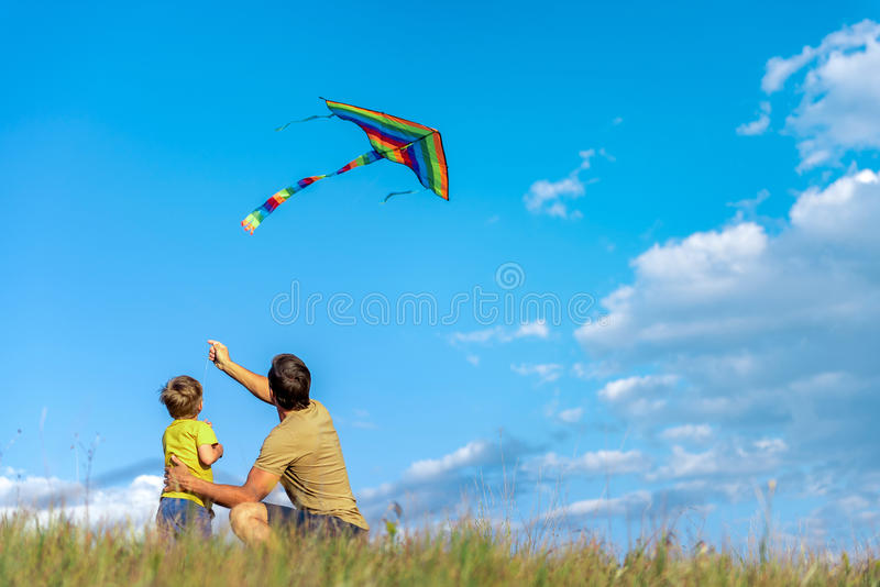 Cheerful boy and man playing with flying toy on field stock image