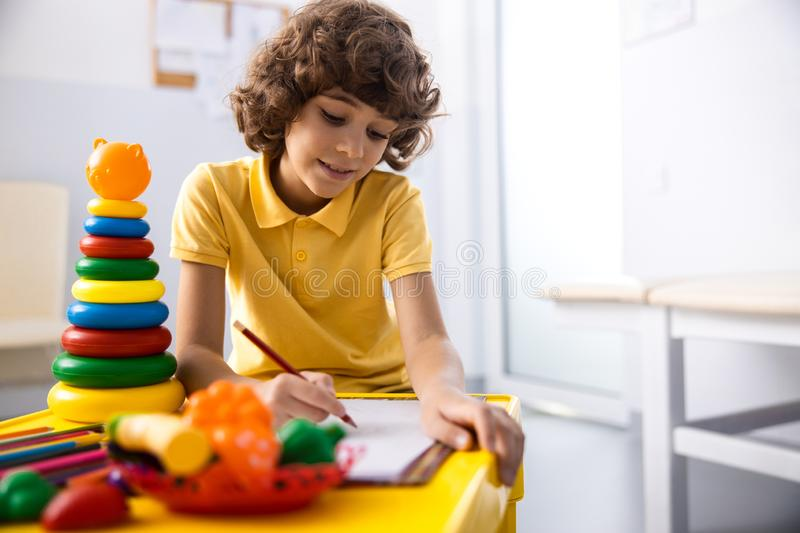 Cheerful boy is painting in hospital palyroom stock photo. Happy curly kid is using pensils for wasting time before appointment with doctor. Website banner royalty free stock image