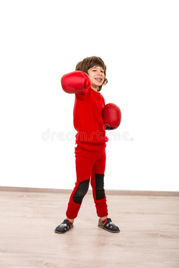 Cheerful boy showing fist in boxing gloves stock photos