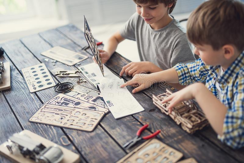 Cheerful boy smiling while his brother pointing to the instruction. Friendly team. Curious enthusiastic brothers sitting at the table and checking the royalty free stock photography