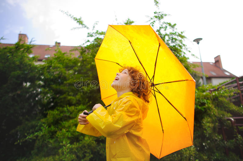 Cheerful boy standing under a yellow umbrella in the yard of the house. The boy in a bright yellow raincoat. The child looks in the sky with a smile. It likes royalty free stock image