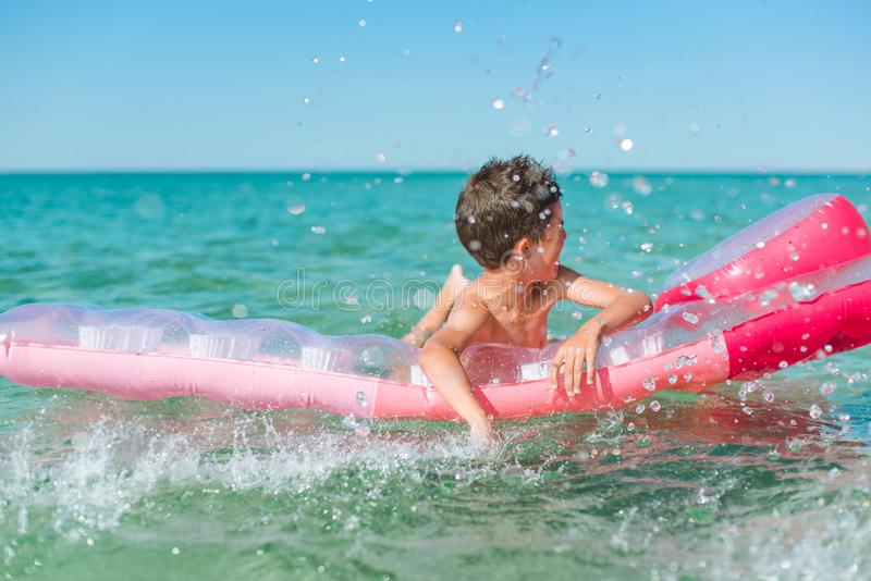 Cheerful boy swims in the sea on a inflatable mattress. royalty free stock photo