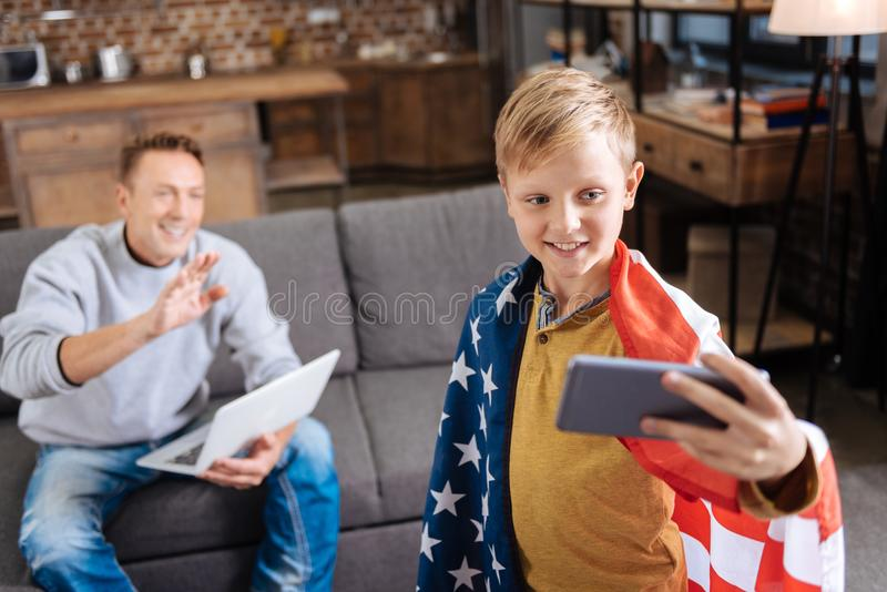 Cheerful boy in US flag taking selfie with his father. Happy family. Cheerful pre-teen boy wearing a US flag on his shoulders and taking a selfie with his father royalty free stock photo