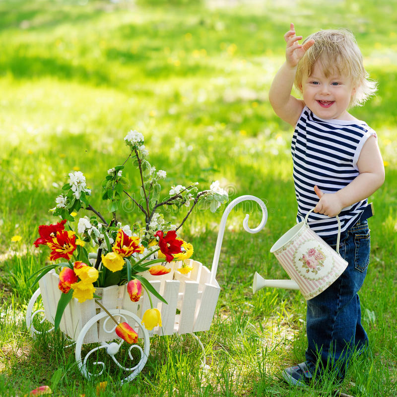 Cheerful boy with watering can and flowers stock photography