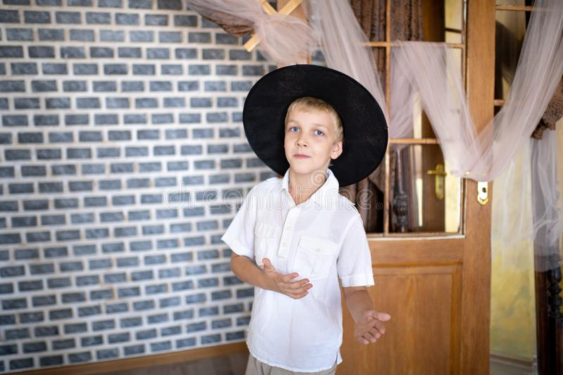 Cheerful boy wearing new wizard hat. Funny cheerful boy wearing new wizard hat. Handsome guy standing near stone wall in an old castle. Cobwebs abandoned rooms royalty free stock image
