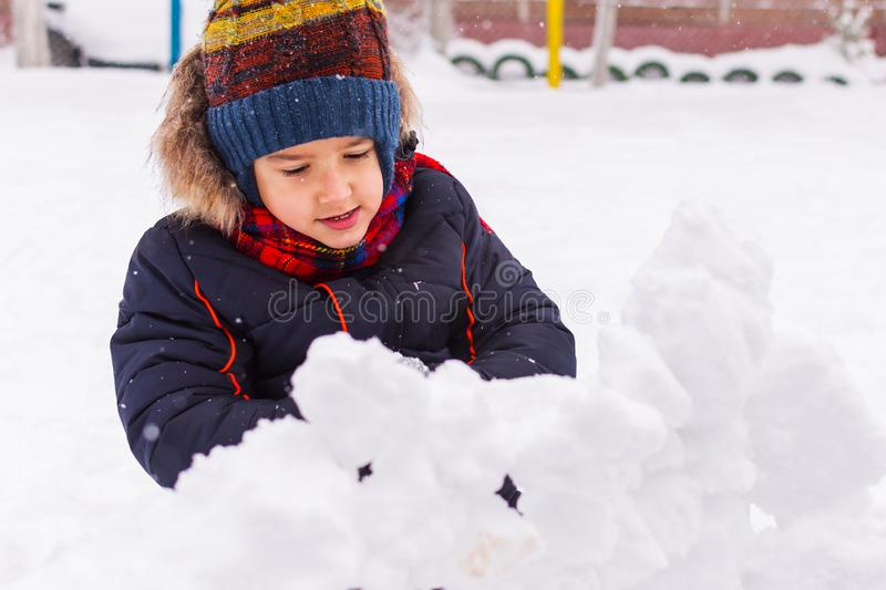 Cheerful boy 5 years old playing in the snow on the Playground royalty free stock photos