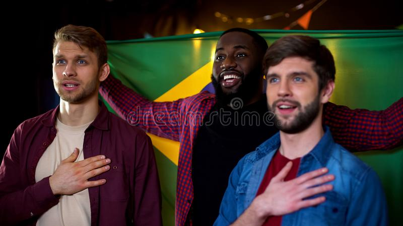 Cheerful brazilian fans holding hands on hearts, listening to anthem, sport. Stock photo stock photos