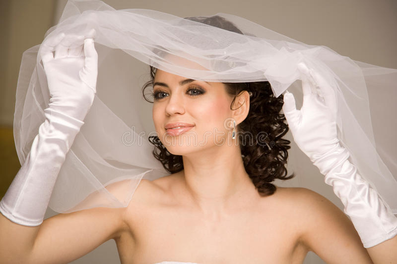 Cheerful bride. Bride enjoying her great day, wind blows her veil stock photo