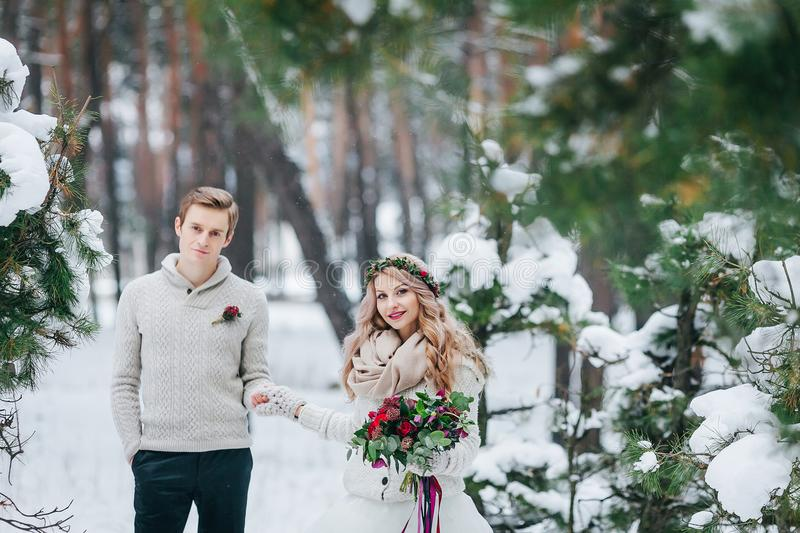Cheerful bride and groom in beige knitted pullovers are walking in snowy forest. Selective focus on bride. Artwork stock image
